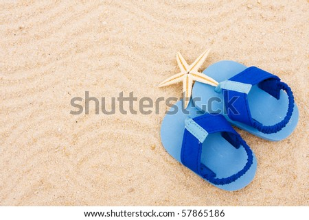 A starfish and a pair of baby?s sandals sitting on a sand background, beach baby