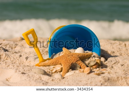 A starfish, shells, and and beach toys set against the crashing surf.  Shot with shallow DOF.