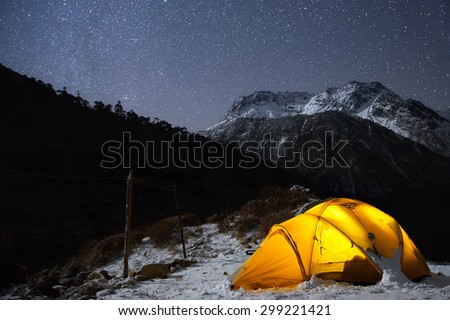 A starry night sky high in the mountains and a tent.