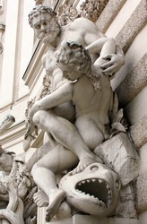 A statue depicting the ancient Greek hero Hercules and his exploits. Sculpture on the facade of a historic old building in Vienna.