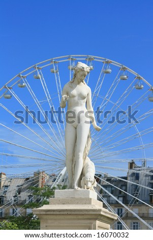 A statue in the Jardin Des Tuleres, Paris. Set against a 'ferris' type wheel to the background, against a clear blue sky, with green foliage and buildings.