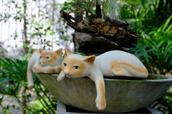 A statue of a cat on the bathtub.
