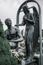 A statue of an angel with a man. High quality photo