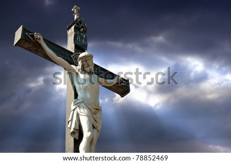 A statue of Jesus Christ crucified against dramatic sky