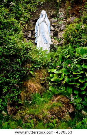 A statue of Virgin Mary on a hill surrounded by foliage
