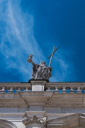 A statue with a cross on the roof of a building with an upward perspective. Italy.