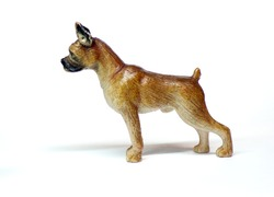 A statuette of a boxer dog isolated on a white background. Dog in profile from the side. Figure and children's toy in the form of a dog.