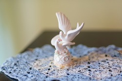 A statuette of white swans on the table.