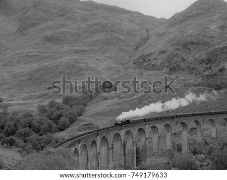 A steam train travels on an arch bridge in the mountains, black and white