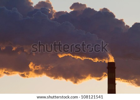 A steaming power plant pipe against sunset sky