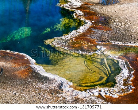 A steaming thermal hot spring pool in the West Thumb Geyser Basin of Yellowstone National Park displays fantastic colors.
