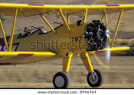 A stearman biplane takes off with a roar of its big radial engine