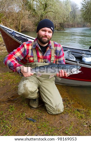 A steelhead fisherman holds his trophy fish by his boat and the river in Oregon.