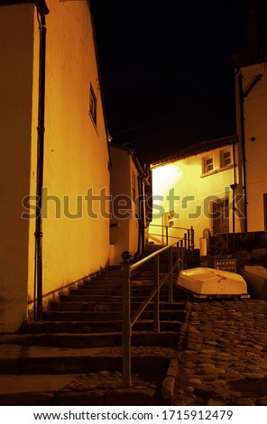 A steep flight of steps leads up beside a cobbled street and an upturned boat in a fishing village at night in Northern England.