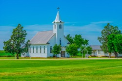 A steepled white church sits in a spring  meadow in Texas. Trees surround the Christian chapel.