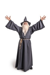 A stern grey-haired bearded wizard in a gray cassock and a cap is practicing sorcery and doing magic against a white background.