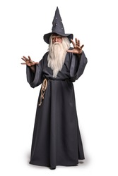 A stern grey-haired bearded wizard in a gray cassock and a cap is practicing sorcery and doing magic against a white insulating background.