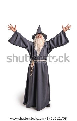 A stern grey-haired bearded wizard in a gray cassock and a cap is practicing sorcery and doing magic against a white background. Сток-фото ©