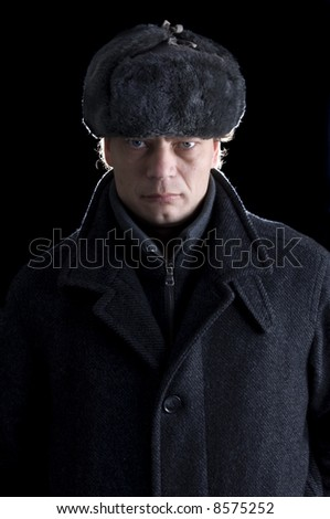 A stern looking man with a fur cap and a woolen coat looking straight into the camera
