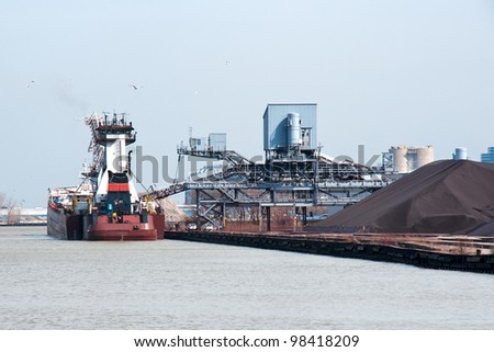 A stern view of an articulated tugboat and barge docked at the Cleveland Bulk Terminal in the Cleveland Harbor on Lake Erie,  The boat is taking on iron ore to be delivered to a steel mill