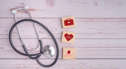 A stethoscope and wooden blocks with icons of health laid on wooden table. Close-up photo. Top view. Flat lay with Space for text. Healthcare and medicine with media icons concept.