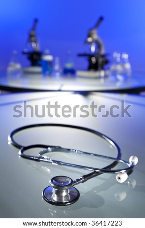 A stethoscope in a medical research laboratory with microscopes, flasks and other equipment in the background