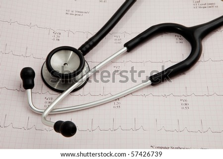 A stethoscope on electrocardiogram report. - stock photo