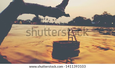 A stick man sailing a boat at evening in a river. That pic was taken at a perfect condition and timing.