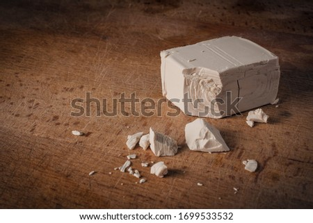 A stick of fresh yeast (brewer's yeast), used for bread and pizza doughs, on a wooden cutting board Stock fotó ©
