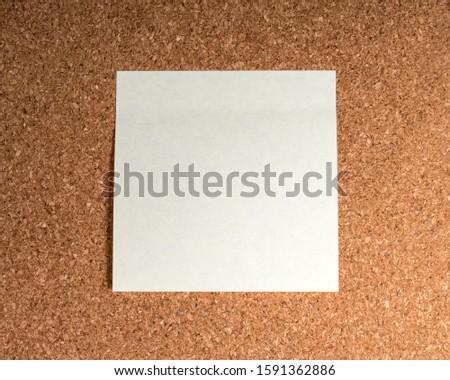A sticky memo note stuck onto a notice board.