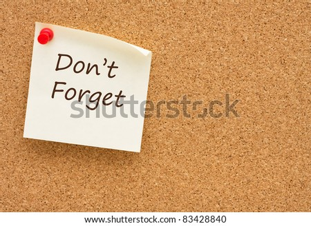A sticky note on a cork board with the words do not forget on it