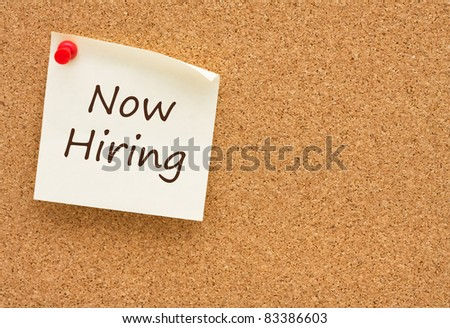 A sticky note on a cork board with the words now hiring on it