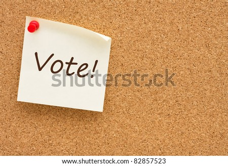 A sticky note on a cork board with the words vote on it