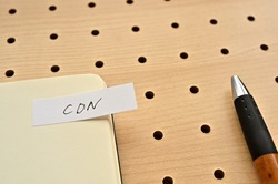 A sticky note with CDN written on the edge of an open notebook on the punching board. That's an acronym for Content Delivery Network.