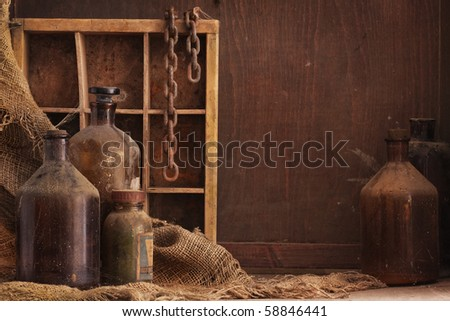 a still life composition with old dusty bottles and other objects on wood background, empty space for text