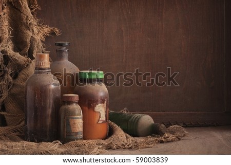 a still life composition with old dusty bottles on wood background, empty space for text