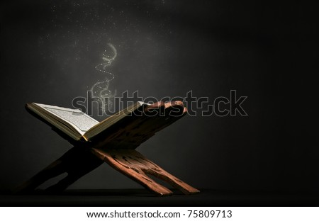A still-life image of Koran (Holy Book of Muslims) on dark black background, with sprinkles falling on. - stock photo