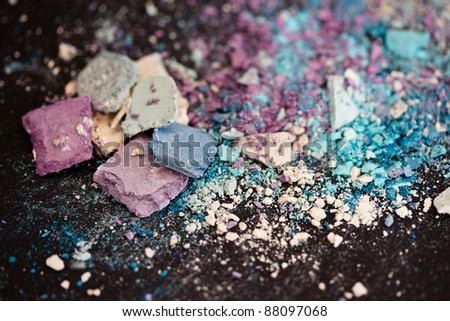 a still-life of colorful eyeshadow powders and make-up