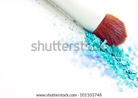 a still-life of colourful eyeshadow powder and make-up brush