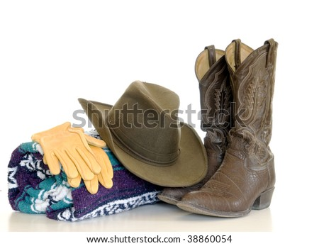 A still life of cowboy boots with a brown cowboy hat and leather gloves atop a green, purple and white blanket isolated over white.