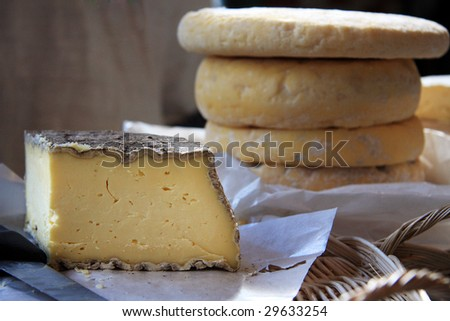 A still life of French cheeses for sale at a market