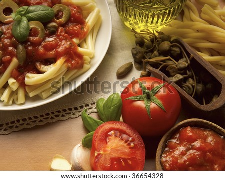 A Still life of Tomato souce and Pasta, oil, bread, garlic and basil - stock photo