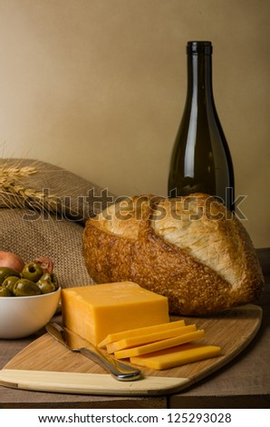 A still life with sausage cheese olives wine bottle and bread on a cutting board