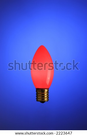 A stock image of a traditional red Christmas bulb. The bulb is lit and on a cobalt blue background.