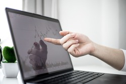 A stock investor is pointing to a laptop screen running a stock chart program to read stock price charts, analyze purchases. Cryptocurrency stocks are popular with both new and old investors.