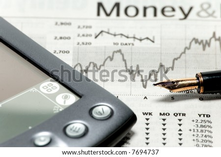 a stock market chart with a pen and pda