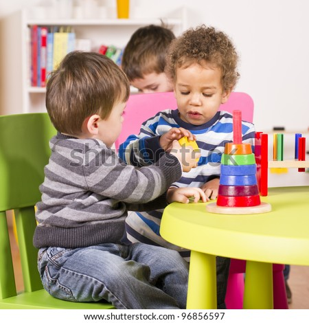 A stock photo of a caucasian and african american child sharing in the play room - stock photo