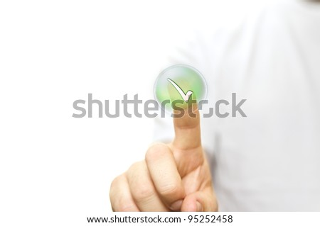 A stock photo of a man in a white t- shirt pressing a button green tick with his finger