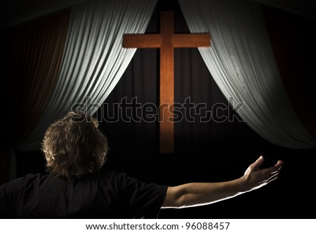 A stock photo of a young man praying with open arms before a cross.