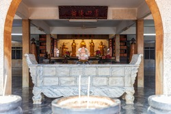 A stone altar with buddhist religious statues i the buddhist temple. This place of worship was found in Malacca, Malaysia. The text around the temple are various prayers.